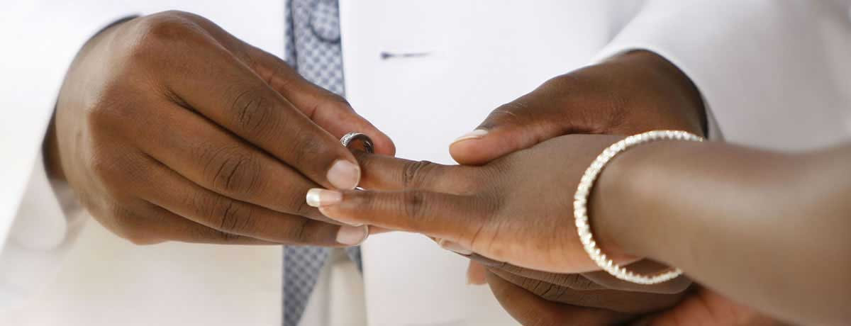 Wedding couple exchanges rings during vows