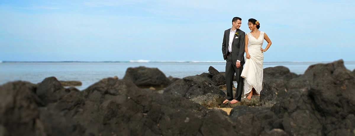 Wedding couple on the black rocks of the beach in Hawaii